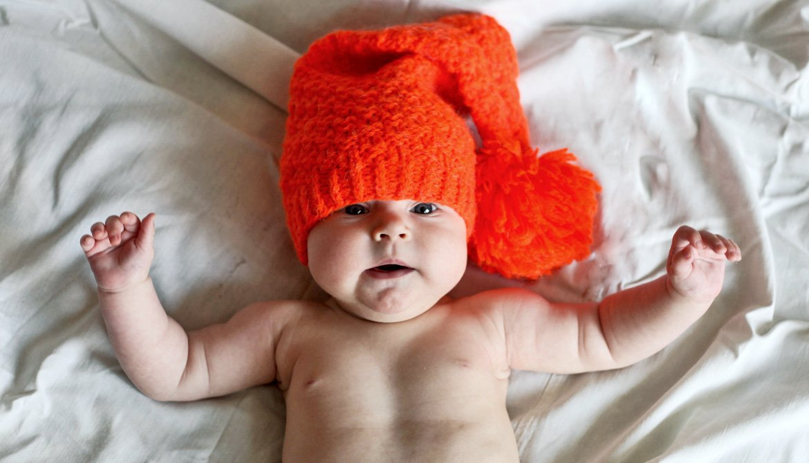 baby wearing orange knit hat