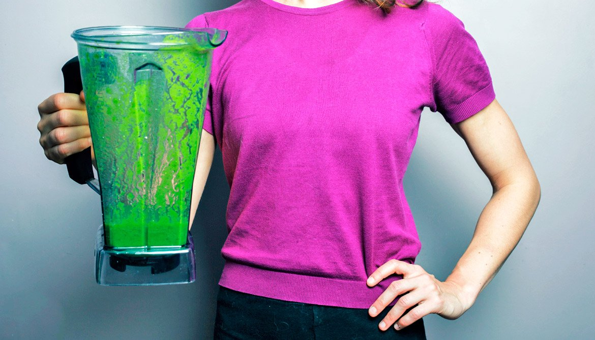 woman hold blender of green smoothie