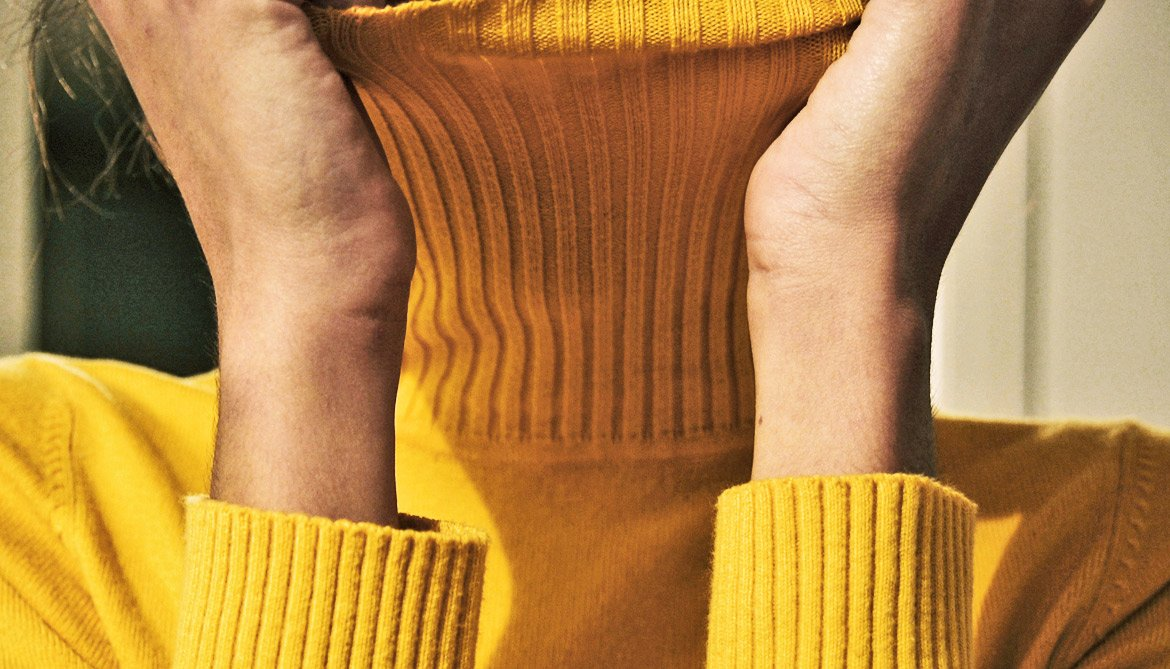 yellow sweater covers neck