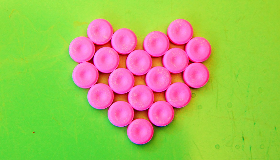 pink tablets in heart on green
