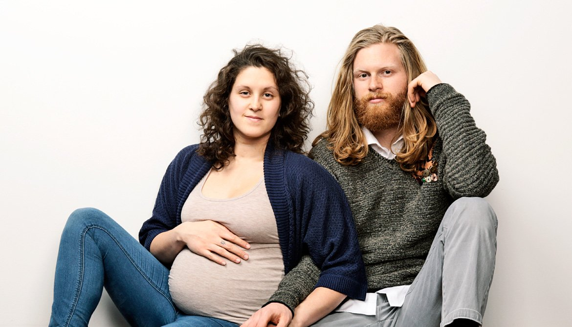 pregnant couple looks serious