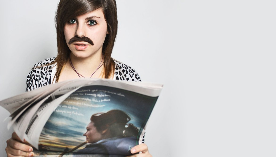 woman with mustache holds newspaper