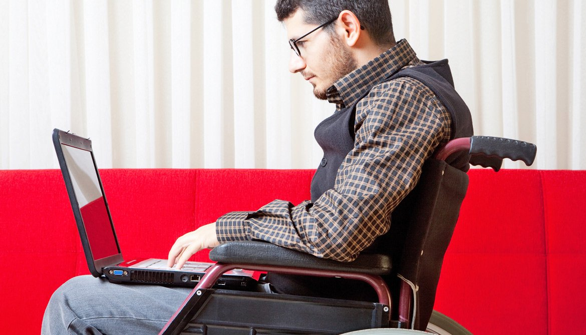 man uses wheelchair & laptop