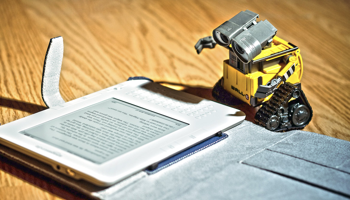 Toy Wall-E robot reading an E-book.