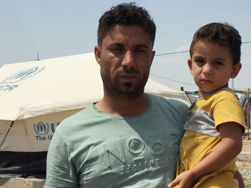© UNHCR/C. Gluck - Khairallah Farhan holds a child at Al Salam camp for displaced families, Baghdad, Iraq.