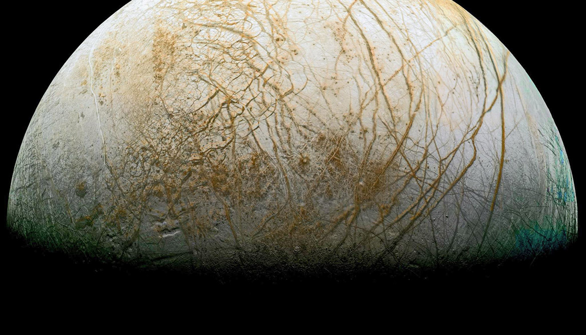 Long, linear cracks and ridges crisscross Europa's surface, interrupted by regions of disrupted terrain where the surface ice crust has been broken up and re-frozen into new patterns. (Credit: NASA/JPL-Caltech/SETI Institute)