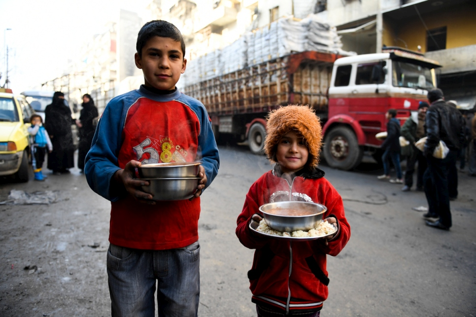 Displaced children carry cooked meals provided by a local charity in the Al-Mashatiyeh neighborhood of east Aleppo, Syria, where UNHCR and its partners are distributing key relief items. © UNHCR/Bassam Diab