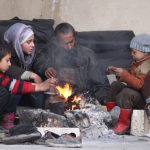 A displaced father and his children try to warm themselves around a fire at Jibreen Collective shelter in Aleppo. © UNHCR/Hameed Maarouf