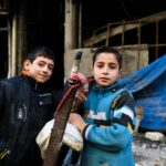 Children stand in front of a destroyed building in the Al-Mashatiyeh neighborhood of eastern Aleppo. © UNHCR/Bassam Diab