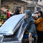 A woman and her two children push a cart carrying relief items distributed by UNHCR and other UN partners in the Tariq Al-Bab neighborhood in eastern Aleppo. © UNHCR/Bassam Diab