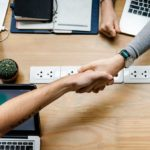 Two people handshaking on a coworking table